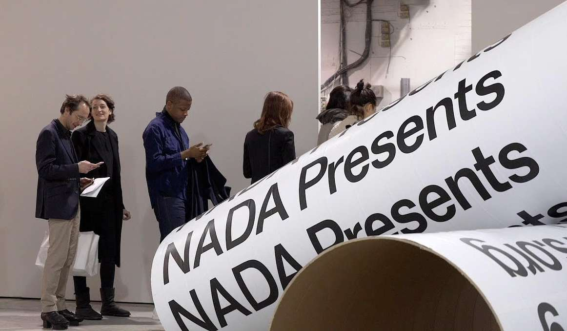 Nada Art Fair with people queueing behind a large rolled banner